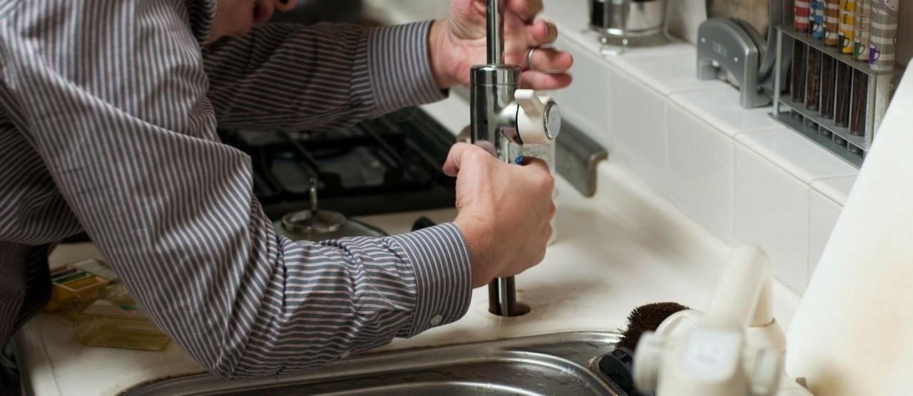 Hydraulik naprawiający baterię w zlewie kuchennym